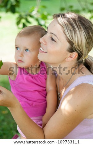 Young mother playing with her baby girl outdoors in the garden - stock photo