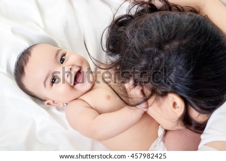 Young mother playing with her baby on white silk bed sheet. Cute mixed race bab boy has fun with mum, high key. - stock photo