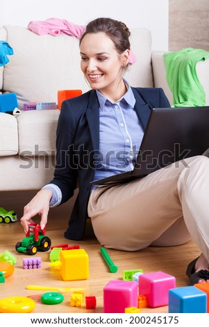 Young mother playing with her child and checking e-mail - stock photo