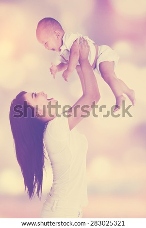 Young mother playing with her little daughter and lift up the baby, shot with blur background