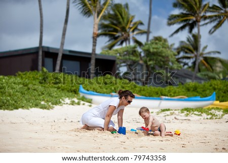 Young mother playing with her little son on a tropical beach - stock photo