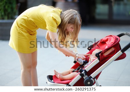 Young mother playing with her little son outdoors - stock photo