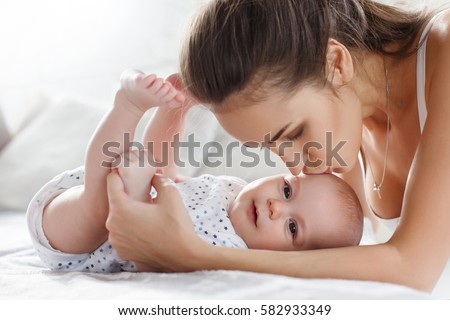 Young mother playing with her 8 months old little son at the bedroom. Young mother playing with her baby son at home. mother playing with baby. Portrait of a happy mother hugging cute baby on bed