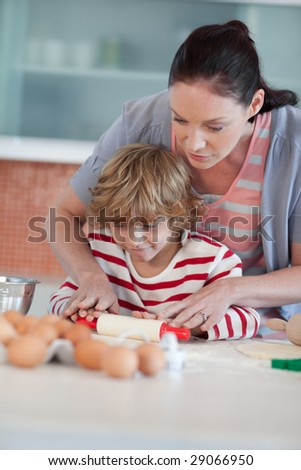 Young Mother playing with her Son in the kitchen - stock photo