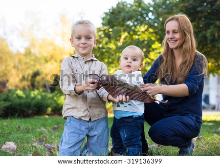 Young mother playing with her sons in the park