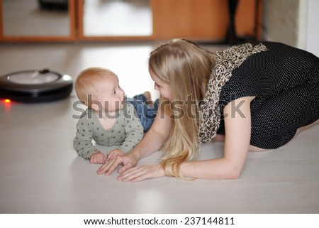 Young mother playing with her toddler son at home - stock photo