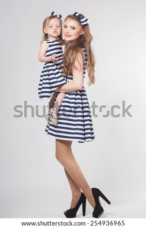 Young mother playing with little daughter - stock photo
