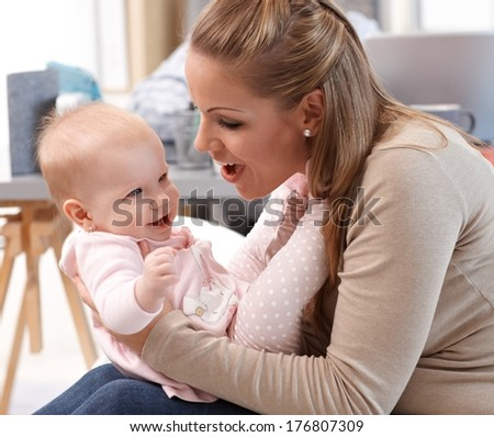 Young mother playing with little girl at home, both having fun.