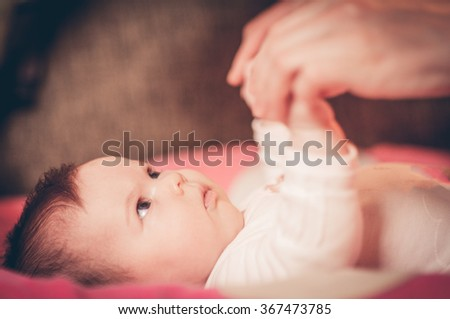 Young mother playing with three months old baby girl