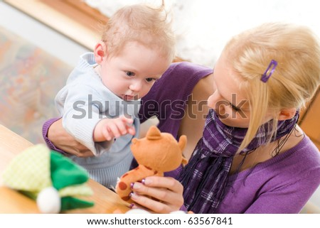young mother plays with her baby with toys - stock photo