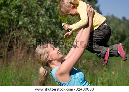 Young Mother Plays with his Daughter - stock photo