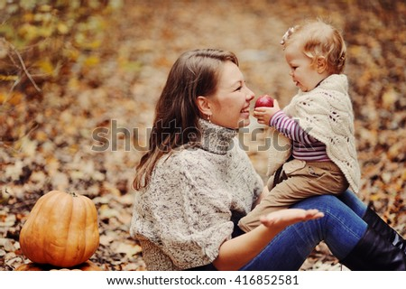 young mother plays with the own child in a warm knitted sweater in autumn park near pumpkin