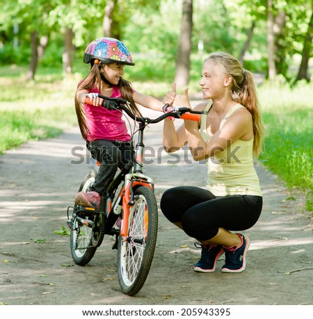 young mother praises her daughter, who learned to ride a bike - stock photo