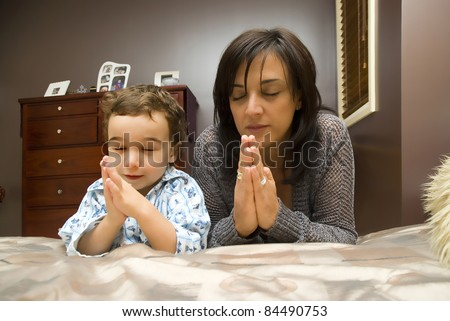 Young mother praying with child - stock photo