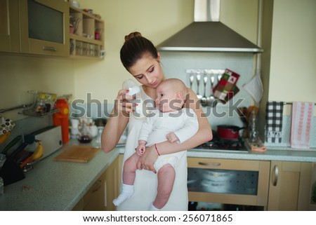 young mother prepares meal in bottle for baby - stock photo