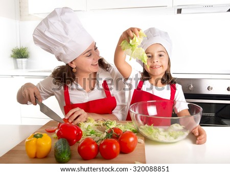 young mother preparing salad for lunch wearing apron and cook hat at home kitchen with little daughter playing with lettuce and having fun together in healthy nutrition education concept - stock photo