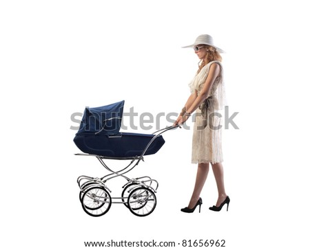 Young mother pushing a pram - stock photo