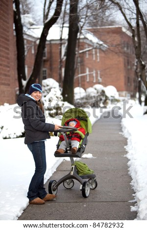 Young mother pushing a stroller with a baby on a warm winter day