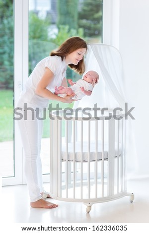 Young mother putting her newborn baby to sleep in a white round crib with canopy next to a big window - stock photo