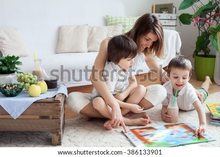 Young mother, read a book to her tho children, boys, in the living room, eating fruits and drinking smoothie, mothers day concept  - stock photo