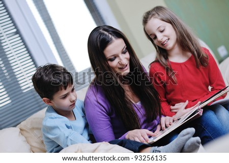 young mother read book to their kids at modern new home living room indoor - stock photo