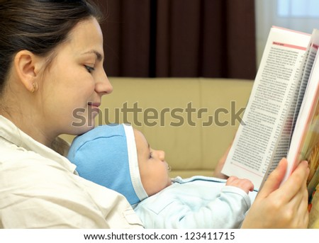Young mother reading a book together with her baby - stock photo