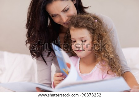 Young mother reading a book with her daughter