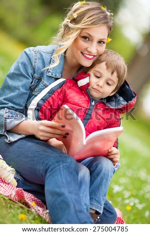 Young mother reading to her son in a park - stock photo