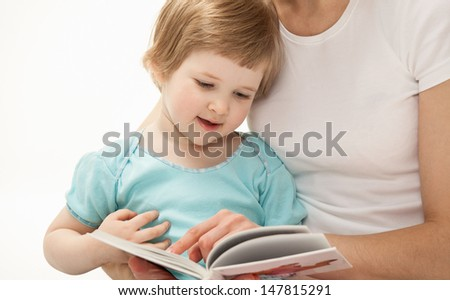 Young mother reading with her little daughter