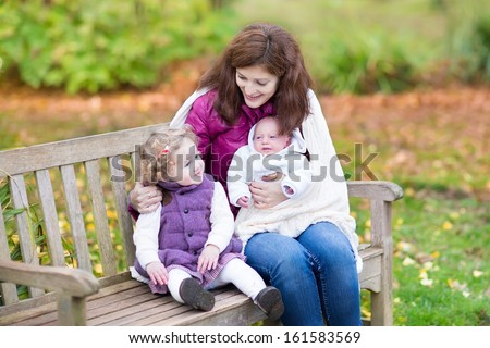 Young mother relaxing on a wooden bench in a colorful autumn park with her toddler daughter and newborn son covered with a white knitted warm blanket - stock photo