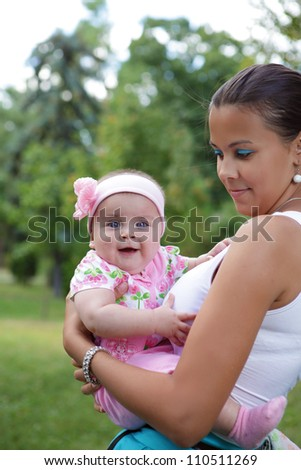 young mother relaxing outdoors looking happy and smiling holding her baby - stock photo