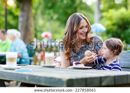 Young mother relaxing together with her little child, adorable toddler girl, in summer outdoors cafe drinking coffee and eating muffin or cupcake. - stock photo