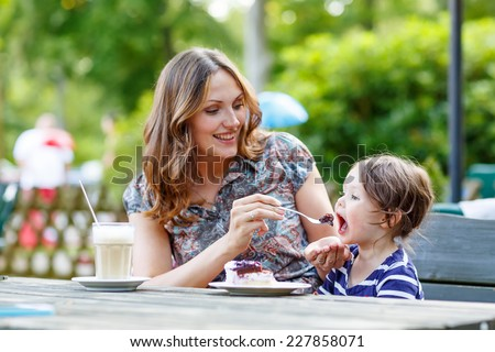 Young mother relaxing together with her little child, adorable toddler girl, in summer outdoors cafe drinking coffee and eating muffin or cupcake. Selective focus on child. - stock photo