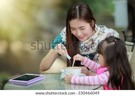 Young mother relaxing together with her little child  girl in summer outdoors - stock photo