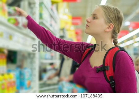 Young mother shopping juices in supermarket