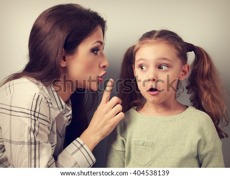 """Young mother showing the finger the silence sign to her surprising daughter and talking """"don not speak the father"""". Toned vintage closeup concept portrait - stock photo"""