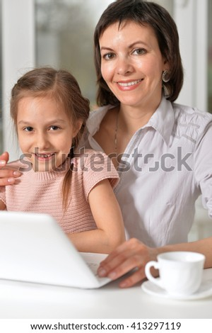 young mother sitting at the computer with a small daughter - stock photo