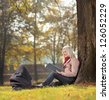 Young mother sitting in a park reading a book with a baby in a carrycot, shot with a tilt and shift lens - stock photo