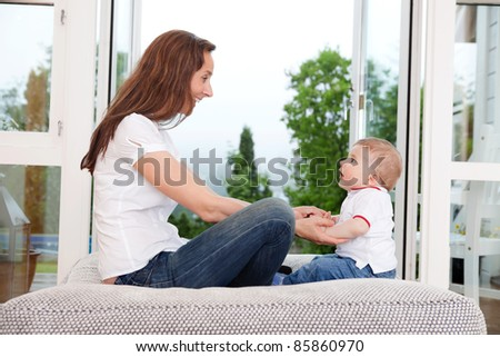 Young mother sitting on couch and looking at innocent child - stock photo