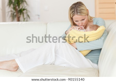 Young mother sitting on the couch kissing her baby in her arms - stock photo