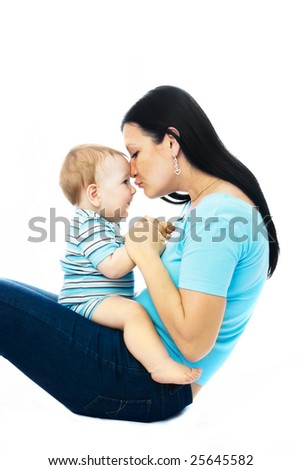 young mother sitting on the floor with her ten months old baby - stock photo