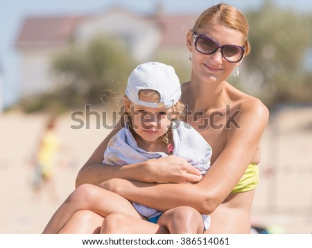 Young mother sitting with frozen five year old daughter on the beach and cherishes it wrapped in a towel - stock photo