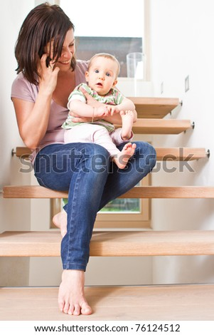 Young mother sitting with her baby on stairs while talking on the cellphone. - stock photo