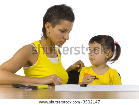 Young mother sitting with sad daughter at desk. Girl looking at mother. White background - stock photo