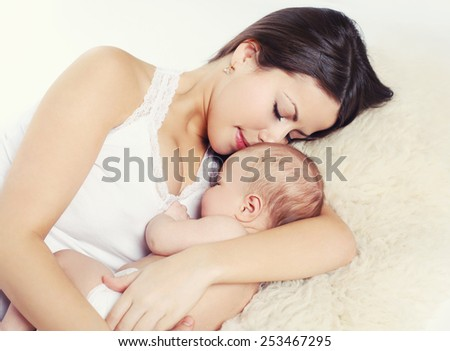 Young mother sleeping with baby at home - stock photo