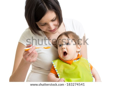 young mother spoon feeding her baby - stock photo