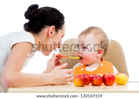 young mother spoon-feeding her baby girl - stock photo