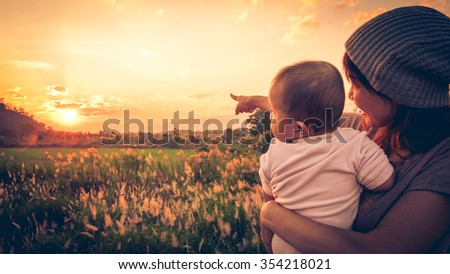 Young mother standing near a river & carrying her baby looking at the beautiful Sunset. Also Seeing a beautiful green field & mountain on a background. Mother pointing her baby see the Sun. - stock photo