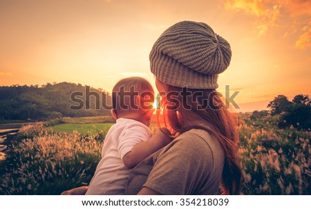Young mother standing near a river & carrying her baby looking at the beautiful Sunset. Also Seeing a beautiful green field & mountain on a background.  - stock photo