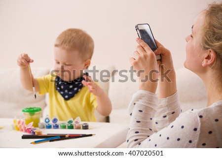 Young mother taking photo of cute little toddler boy in yellow shirt sitting at table and drawing with colorful paints. Early learning. Creative. Toddler drawing. Mom making picture on mobile phone - stock photo